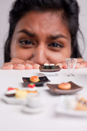 big girl: funny picture of an indian girl dieting with symbolic little pieces of food