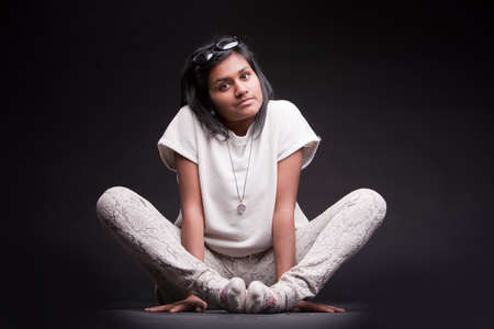 crouched: portrait of a crouched indian girl serious Stock Photo