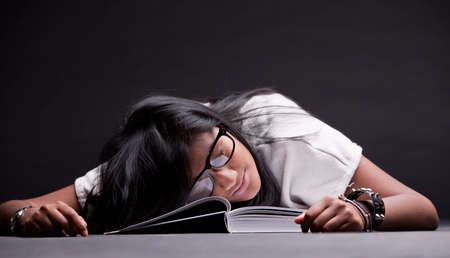 indian girl sleeping tired of studying on an open book photo