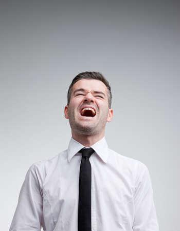 laughing out loud: hombre riendo a carcajadas con una corbata sobre un fondo neutro