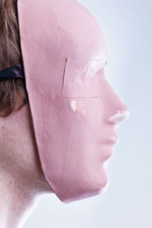 awkwardness: man with mask in a foreground portrait brightly lit