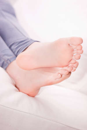 foot fetish: clean pair of feet of a girl on a white sofa