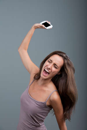 woman angry: mujer enojada que lanza un tel�fono m�vil