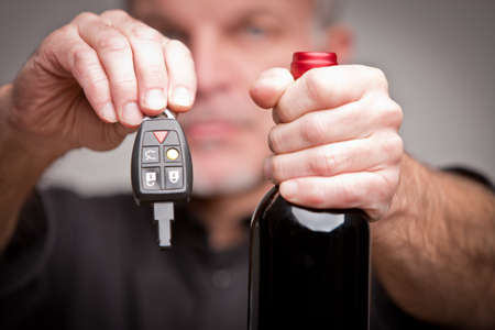 dodgy: hands with car keys and a bottle of wine symbolizing alchool problems and accidents