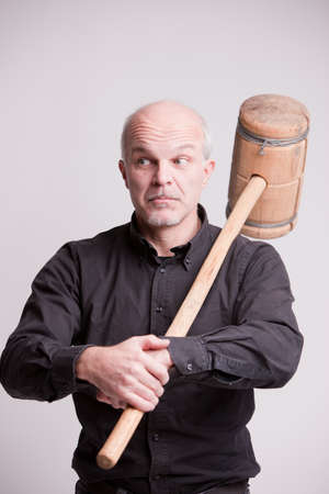 indifferent: suspect man with a wooden big hammer pretends to be indifferent Stock Photo