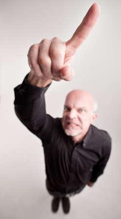 berisping: senior man berisping met een vinger stijgt in de lucht in een zeer ernstige berisping