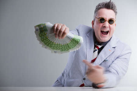 buisness: mad man in suitjacket and sunglasses sitting behind a desk is pointing with his hand full of rings a lot of money wich he keeps in the front with the other hand shouting something.