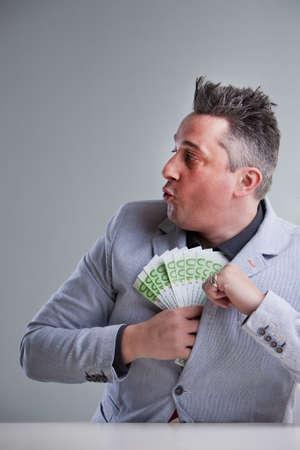 Dodgy buisness Mann versteckt sich viele Banknoten in seinem suitjacket mit nonchalant gerade nach rechts Sicht. Standard-Bild - 35251185