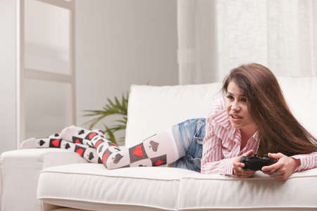 absorbed: pretty girl absorbed playing videogames at home on her sofa in her living room Stock Photo