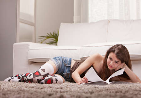 lolita: pretty girl reading a book on her rug in front of her sofa in her living room