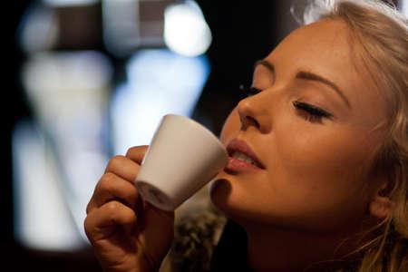 tastes: a blonde woman tastes really good her coffee in a bar or a coffee shop