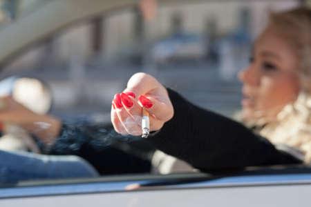 person smoking: una mujer rubia que conduce sacude la ceniza de su cigarrillo por la ventana de su coche Foto de archivo