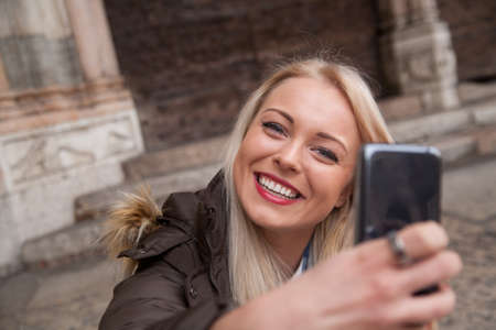 having fun in winter time: young blonde woman taking a selfie or a self portrait with her mobile phone because she may be a tourist in an European city