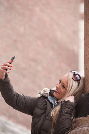 having fun in winter time: blonde tourist making a selfie outdoors in an European City Stock Photo