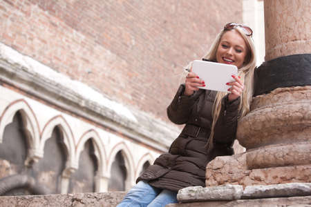 having fun in winter time: blonde smiling tourist girl using a tablet outdoors in an European city