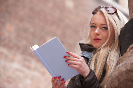 having fun in winter time: blonde young woman reading a book outdoors maybe in an European city of art