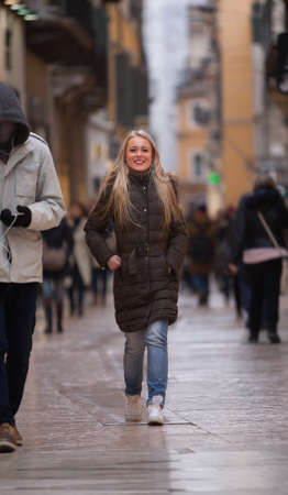 having fun in winter time: blonde tourist young woman shopping happily in Europe