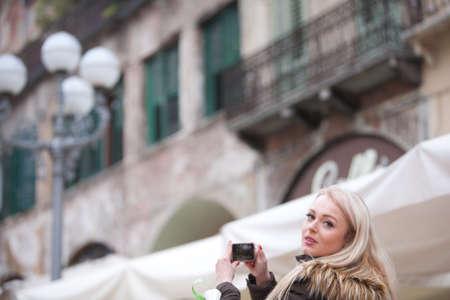having fun in winter time: blonde tourist taking photographs in an European City