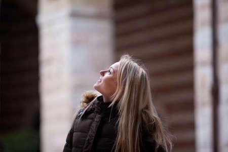 having fun in winter time: blonde young woman touring and enjoying an European city