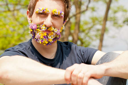 compatible: young self-confident man looking at camera with his eyebrow and beard disguised with flowers Stock Photo