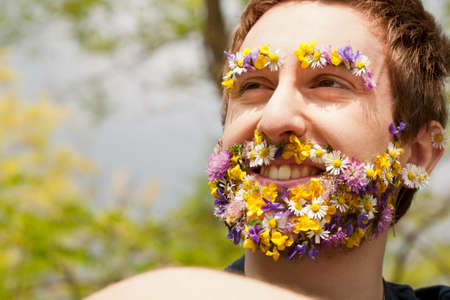 face covered: young man with his face covered with flowers and an hipster appereance smiling outdoors