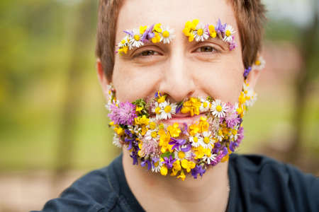 happy hipster man in the nature with flower beard and eyebrows smiling Stock Photo