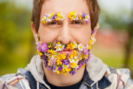 self confident: young hipster man with his beard and eyebrows covered with flowers looking at camera with a sly smile but very self confident