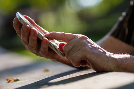 old person: aged finger of an old person pressing on a mobile phone smartphone