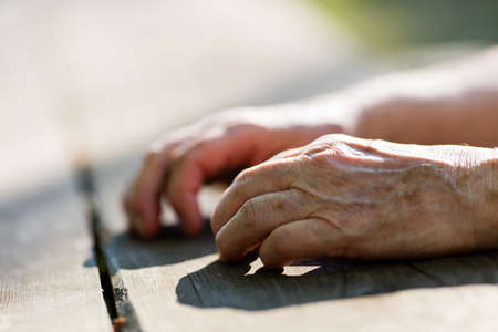old person: aged hands of an old person on a table waiting relaxed