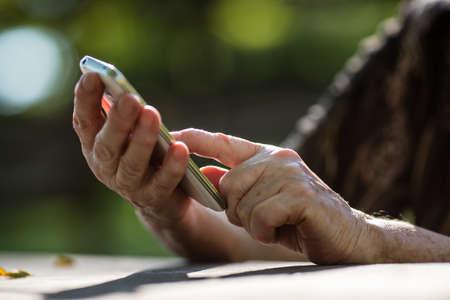 leeftijd vinger van een oude persoon te drukken op een mobiele telefoon smartphone