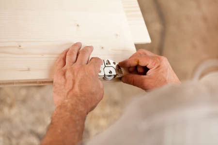 trustful: hands of a carpenter placing a metallic component on a wooden board thats part of a piece of a hand made furniture