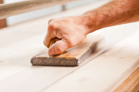 hand crafted: detail of a carpenters hand wood-smoothing with belt sander Stock Photo