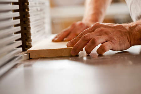 moulder: robust hands of a man working on a wood shaper (spindle moulder) in a carpenter workshop, detail of a board being shaped
