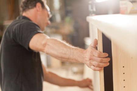 carpintero: poderoso brazo y de la mano de un carpintero colocación de un componente en una pieza de la pieza artesanal de muebles Foto de archivo
