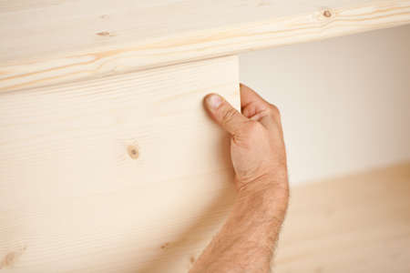detail of a thimb of a powerful arm and hand of a carpenter placing a component in a piece of handcrafted piece of furniture