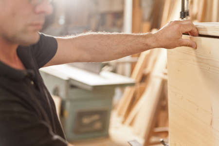 handcrafted: arm and hand of a carpenter carefully placing a component in a piece of handcrafted piece of furniture Stock Photo