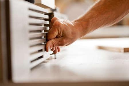 moulder: robust hands of a man working on a wood shaper (spindle moulder) in a carpenter workshop, detail of the hand adjusting the machine
