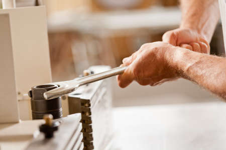 trustful: robust carpenters hands fastening with a wrench in his workshop to adjust a spindle moulder (or wood shaper)