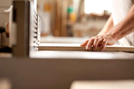 moulder: robust hands of a man working on a wood shaper (spindle moulder) in a carpenter workshop, detail of the hand holding a board