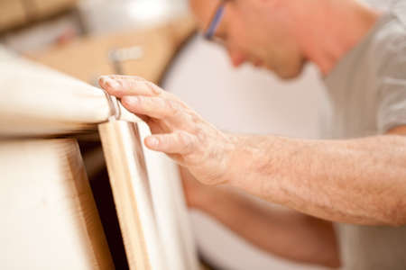 handcrafted: focus on the robust hand of a carpenter placing a flap (a wooden board) on a piece of a handcrafted wooden piece of furniture