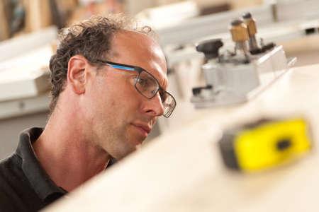trabajando duro: carpintero altamente enfocado en su trabajo en el medio de su taller envuelta con plantillas y cinta de medición fuera de foco