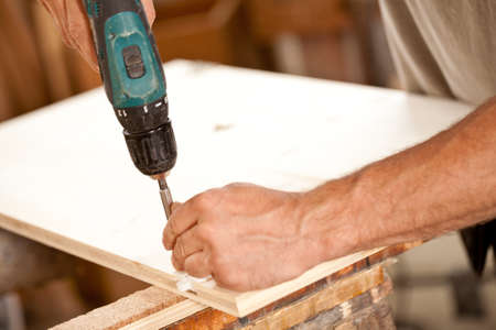 screwing: hand of a carpenter and detail of a drill driver screwing a component in a joiners workshop