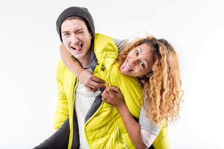 having fun in winter time: happy friends black girl and white boy making faces