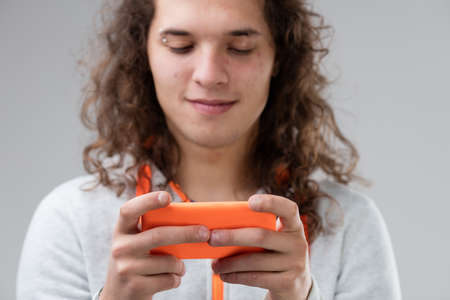 antisocial: long haired young man using an orange smartphone and smiling Stock Photo