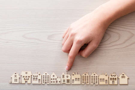 rent index: real hand pointing out a house model among the others mini figures in a micro wooden village set Stock Photo