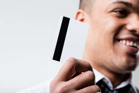 mouth: afro-american man (out of focus) holding a blank credit credit card (editable) and hes smiling