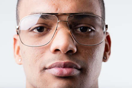 young man portrait: young afro-american man close up portrait with out of fashion glasses in nineties style Stock Photo