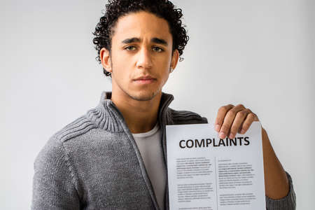 complaints: young man holding complaints sheet and maybe hes a customer or at service