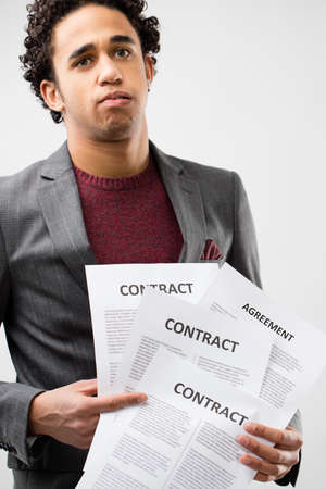 bureaucracy: young business man frustrated by mess of contracts and bureaucracy to deal with