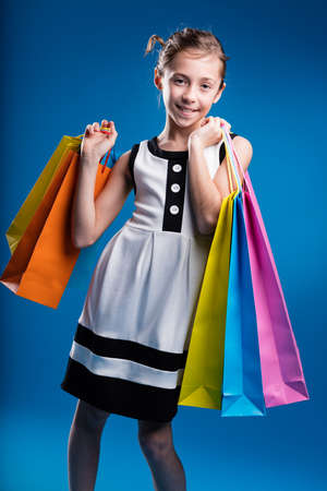 gir: little gir loves to do shopping with lots of coloured bags Stock Photo